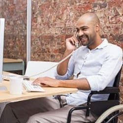man sitting in a wheelchair at his desk talking on the phone while looking at his computer screen