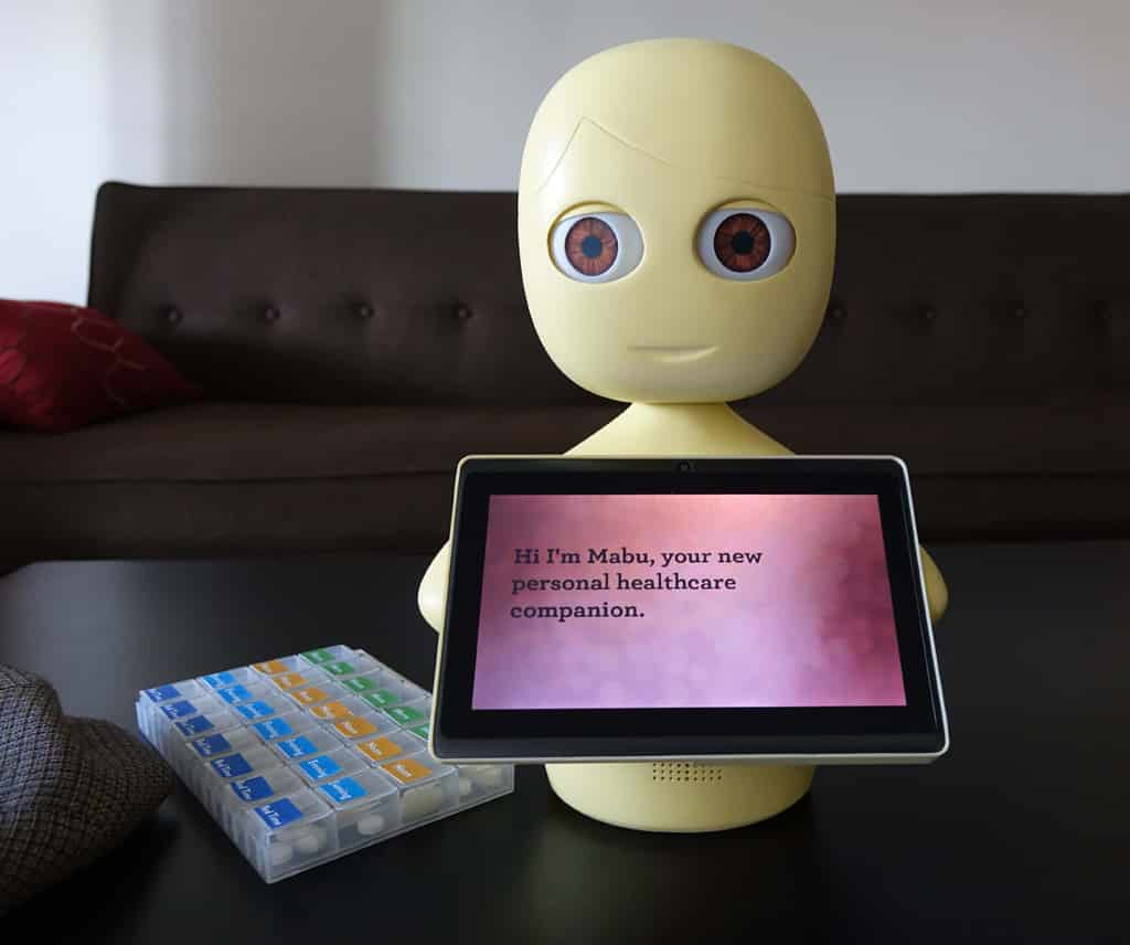 Mabu the robot holding ipad with text for medication reminder