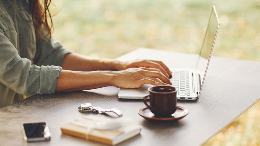 picture of a woman typing on her laptop with a cup of coffee and notepad on her desk