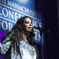 Maysoon-Zayid standing before an audience at a conference waving a hand