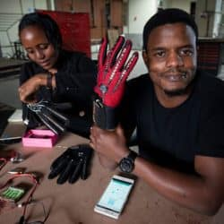 Kenyan engineer is seated at work station holding up the sign language glove wtih his right hand