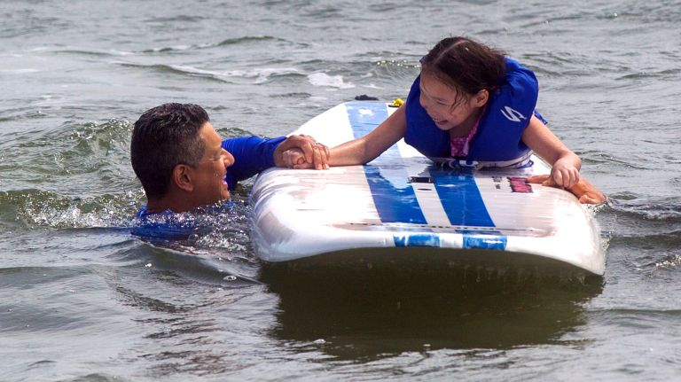 young girl on a surfboard with instructor balancing her in the water