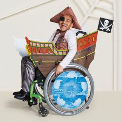 child dressed in pirate costume sitting in decoratedwheelchair