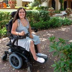 Sylvia Colt-Lacayo outside in her wheelchair wearing a floral dress