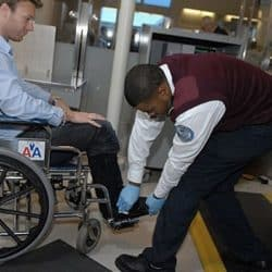 TSA screener checks wheelchair at the airort screening area