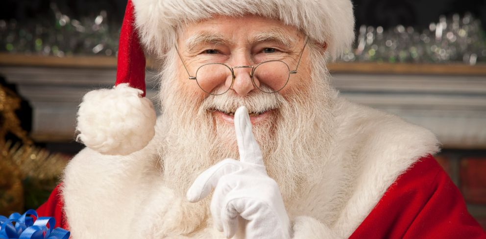 Santa Claus holing a finger up to his lips giving the quiet sign