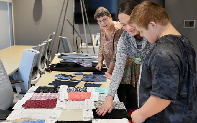 young man with Down Syndrome looks on as two women review clothing laid out on a table
