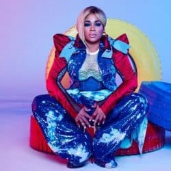 "TLC's Tionne ""T-Boz"" Watkins is pictured sitting on a red chair with a colorful blue and red themed outfit"