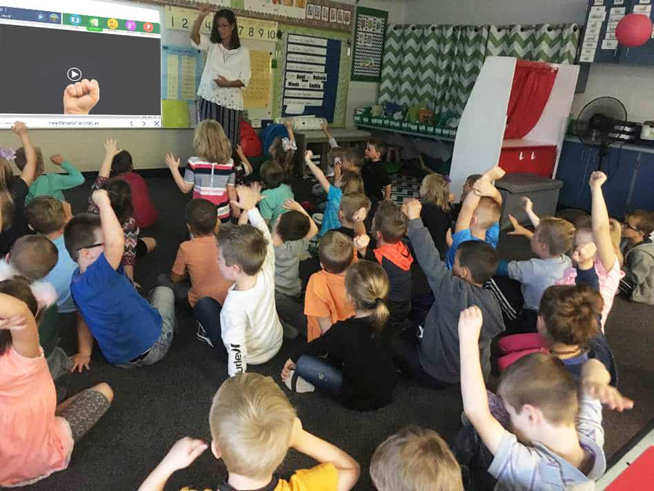 Group of students raising their hands in class