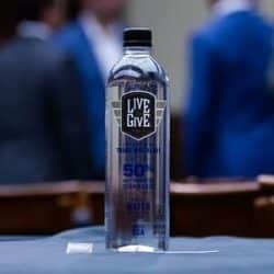 Live to Give bottle of water sitting on a table with blurred image of people in the background