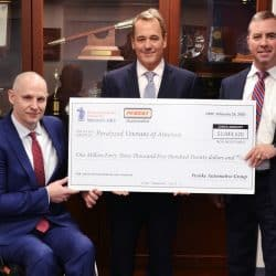Penske representives and man in wheelchair hold big check at check presentation ceremony
