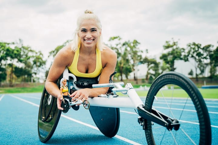 Madison de Rozario is laying down on her racing vehilce smiling towards the camera