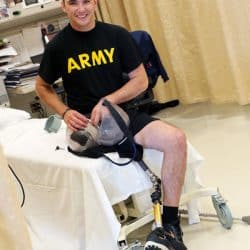 Disabled veteran sitting on a hospital bed with a prosthetic leg