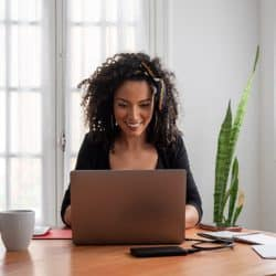 young latin woman working at home with laptop and documents