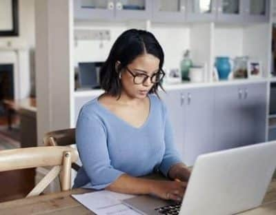 Woman looking at computer while working remotely from home office