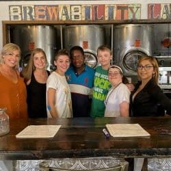 Brewability staff standing together in front of service area with colorful Brewability sign in the background