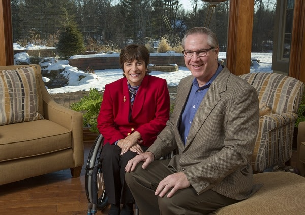 Rosemarie Rossetti and her husband, Mark Leder, sitting in the living room of their home and smiling at the camera