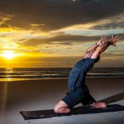 wounded warrior Dan Nevins stretching out on mat doing Yoga at the beach, beautiful sunset in the background yoga