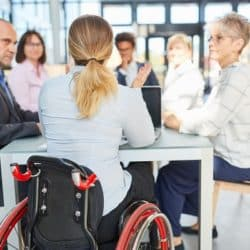 A woman in a wheelchair leading a business meeting