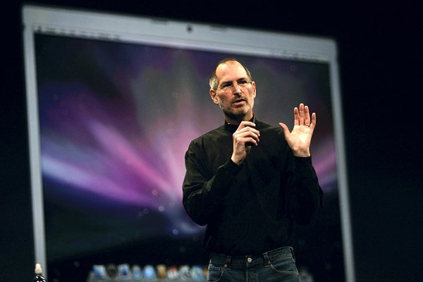 Steve Jobs standing on stage talking into a microphone at a conference