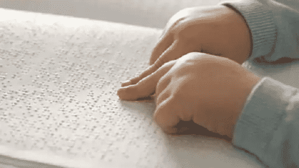 Two hands reading a book in braille
