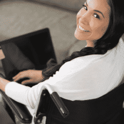 disabled woman in wheelchair smiling looking over her shoulder at camera