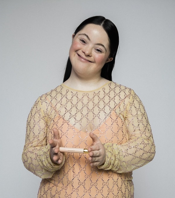 Ellie Goldstein Down Syndrome model poses in gold sequined blouse smiling