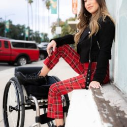 chelsie hill rolettes founder sits on sidewalk ledge of building with a foot up on her wheelchair smiling