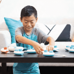 yound disabled boy playing with building blocks on coffee table