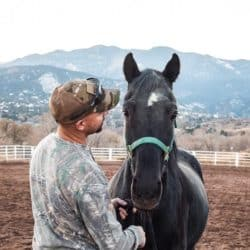 A man wearing camoflague standing next to a black horse