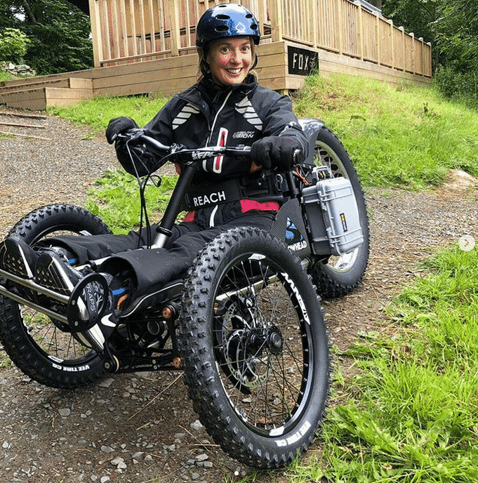 disabled woman sitting on a custom mountain bike wearing a helmet