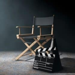 Director chair and movie clapper displayed in an empty room