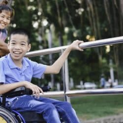 A child in a wheelchair at the park with his mother