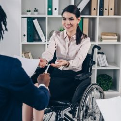 A woman in a wheelchair accepting a pen and paper from a fellow employee
