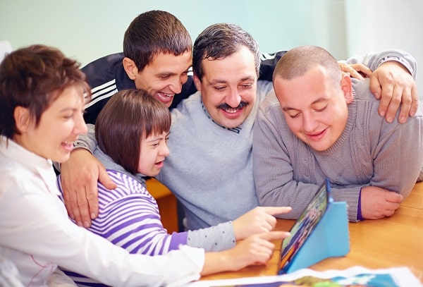A family smiling and gathered around a tablet computer