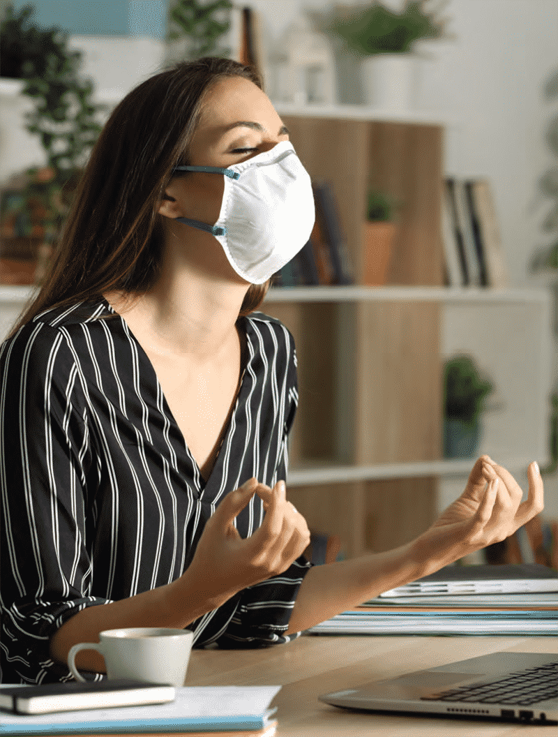 woman wwearing mask at desk in a pensive mediation state