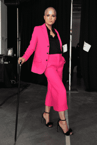 Selma poses backstage in hot pink pantsuit and heels, balncing with a cane and smiling