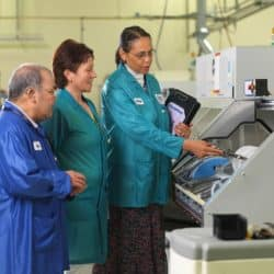female supervisor showing electronic equipment to two students in work facility