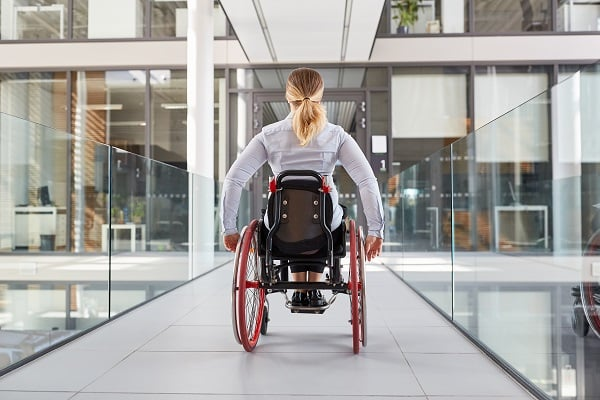 A woman in a wheelchair, going down a hallway