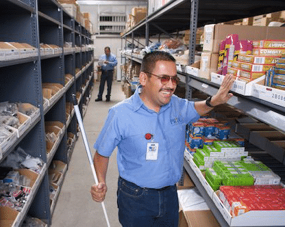Ray Muro, PRIDE Industries employee, shows his workplace accomations in the company warehouse