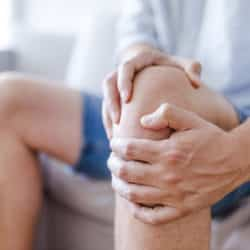 Man suffering from knee pain sitting sofa. A mature man massaging his painful knee. Man suffering from arthritis knee pain at home, closeup. Pain knee