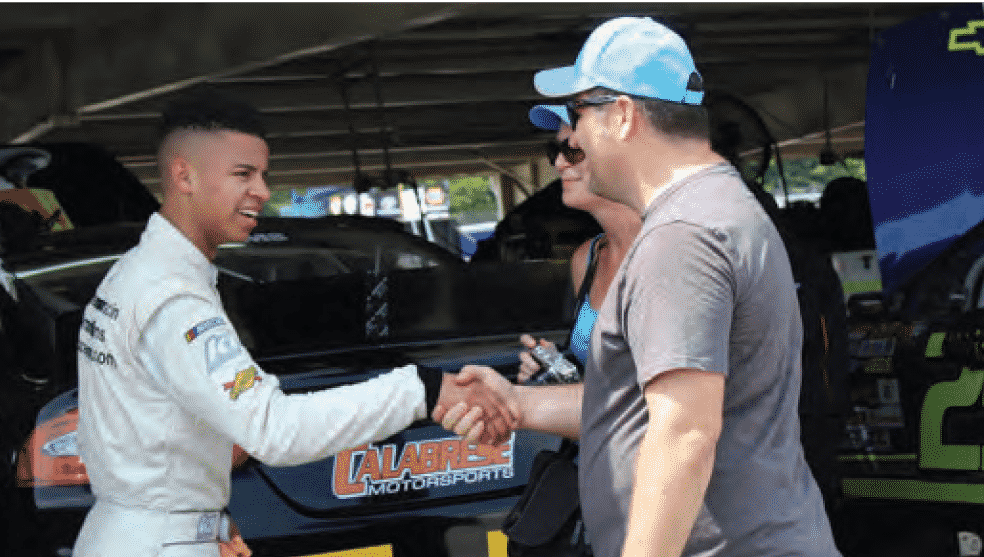 NASCAR driver Armani Williams on the track shaking hands with male spectator