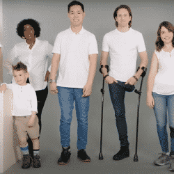 group of people with disabilities standing together in a row modeling different shoes