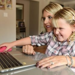 Julia Dapkus and her daughter Isabelle, who has developmental disabilities, work on virtual learning using a fidget mouse.