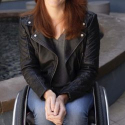 Katherine Beattie sitting is a wheelchair wearing leather jacket and jeans