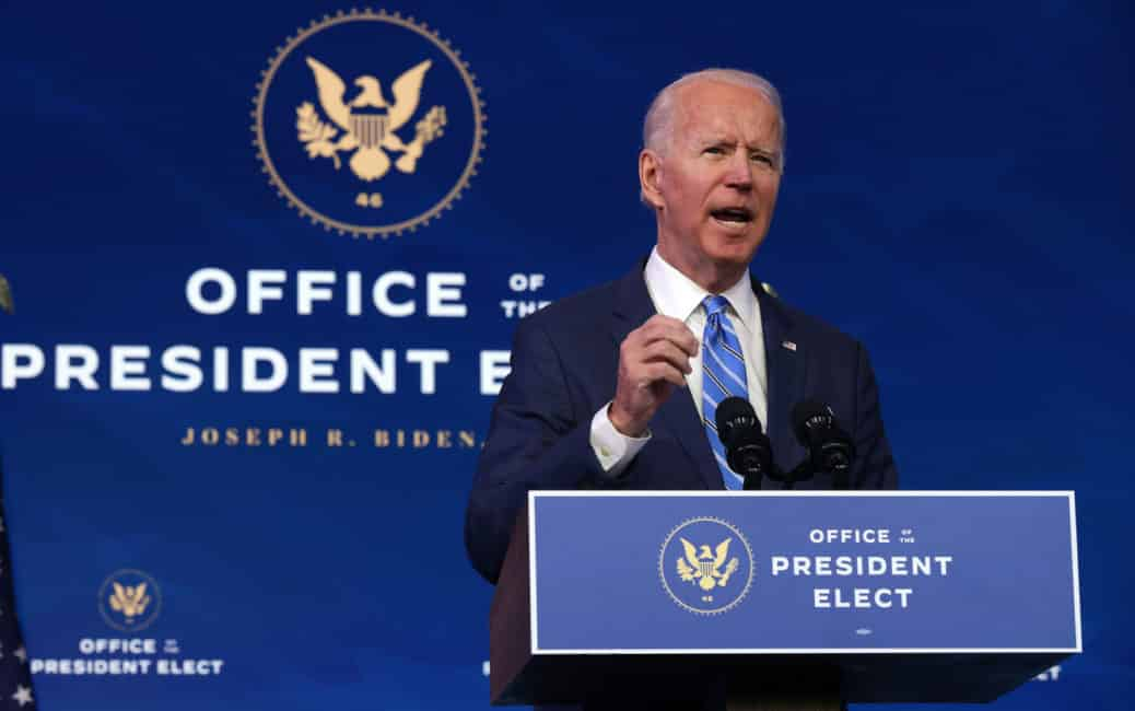 Joe Biden Giving a speech wearing Blue suit and tie