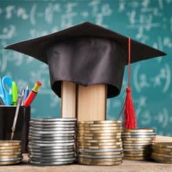 Graduation cap sitting on a pile of giant money coins next to a pencil holder in front of a blackboard