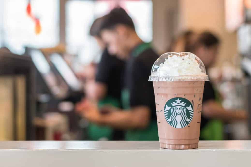 Starbucks drink on table with employees in the background working on the cash register.