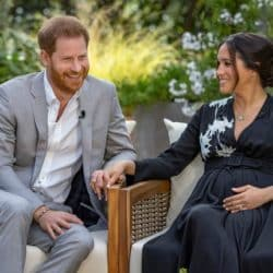 Harry and Meghan Markle seated side by side during an interview while smiling at one another laughing