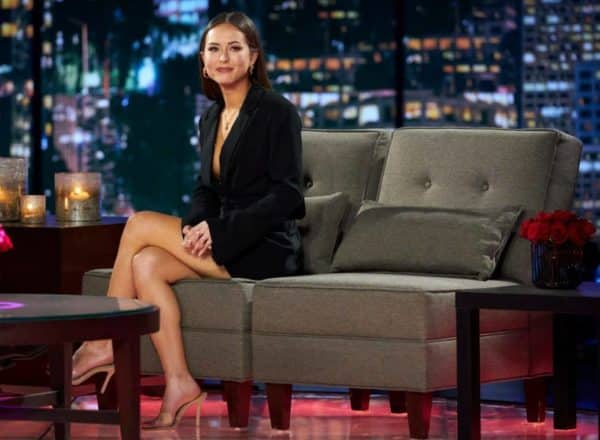 Abigail Heringer wearing a black blazer while seated on a gray couch while on set of a talk show